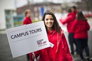 Student Ambassador holding a campus tours sign